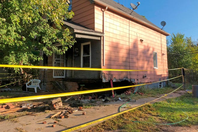 In this Sept. 9, 2019, photo, damage to a home can be seen after a car crashed into it in Detroit. Two people died after their car crashed into the house while the vehicle was being pursued by police. The car burst into flames Tuesday, Sept. 8, 2019, and blew a huge hole in the foundation of the house.