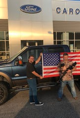 A Ford dealership in South Carolina is giving away flags, Bibles and AR rifles as part of a popular sales promotion. In this image, Christian Frank (left) and James Ashley (right) appear in the company's Facebook post in October 2019.