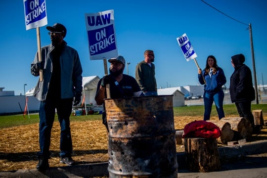 Detroit resident Jay Hawkins, left, and Flint resident Damien Moore picket outside of General Motors' Flint Paint Facility during the nationwide UAW strike against General Motors on Monday, Oct. 7, 2019, in Flint, Mich. Hawkins has 12 years in at the Flint Assembly Plant, while Moore has 11 months in as a temporary worker. (Jake May/The Flint Journal via AP)