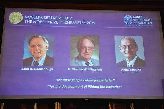 """A screen displays the laureates of the 2019 Nobel Prize in Chemistry, from left, John B. Goodenough, M. Stanley Whittingham, and Akira Yoshino """"for the development of lithium-ion batteries"""", during a news conference at the Royal Swedish Academy of Sciences in Stockholm, Sweden, Wednesday Oct. 9, 2019."""