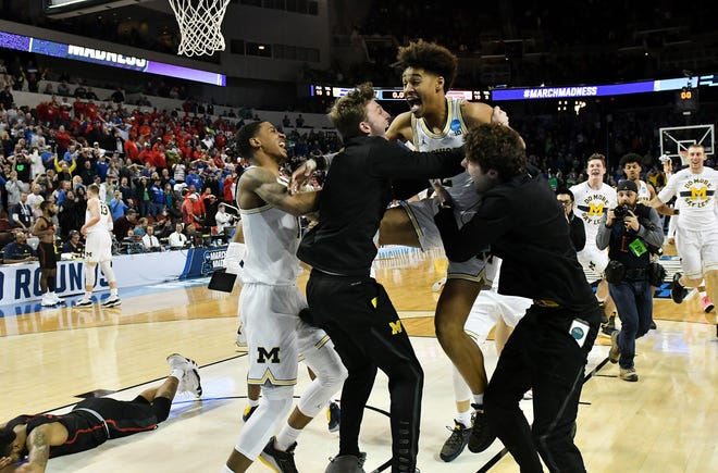 """Former Michigan guard Jordan Poole,  right, says he """"for sure"""" would have been using his name for endorsements after his buzzer beater in 2018 beat Houston in the NCAA Tournament."""