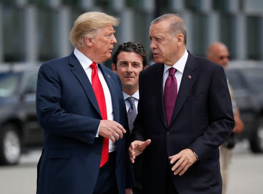 FILE - In this Wednesday, July 11, 2018, file photo, President Donald Trump, left, talks with Turkey's President Recep Tayyip Erdogan, as they arrive together for a family photo at a summit of heads of state and government at NATO headquarters in Brussels. The White House says Turkey will soon invade Northern Syria, casting uncertainty on the fate of the Kurdish fighters allied with the U.S. against in a campaign against the Islamic State group.