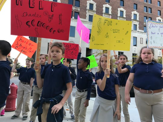 Fourth grade charter school students Lennon Paxton (left) and LeeAnn Turner (right) from Holly Academy on Wednesday, Oct. 9, 2019, protested Gov. Gretchen Whitmer's line item veto that cut a $240 per-pupil increase for charter school students while maintaining the increase for traditional public school students.