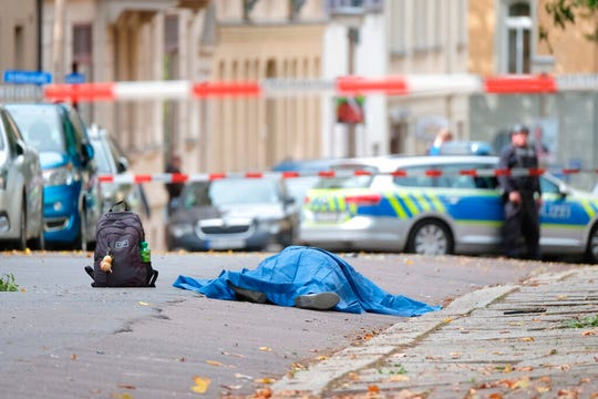 A body lies on a road in Halle, Germany, Wednesday, Oct. 9, 2019 after a shooting incident. A gunman fired several shots on Wednesday in Halle and at least two were killed, according to local media FOCUS online.