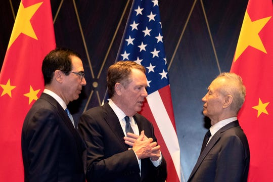 In this July 31, 2019, file photo U.S. Trade Representative Robert Lighthizer, center, gestures as he chats with Chinese Vice Premier Liu He, at right with Treasury Secretary Steven Mnuchin, left, looking on after posing for a family photo at the Xijiao Conference Center in Shanghai. The 13th round of U.S.-China trade negotiations is set to begin Thursday, Oct. 10 in Washington.