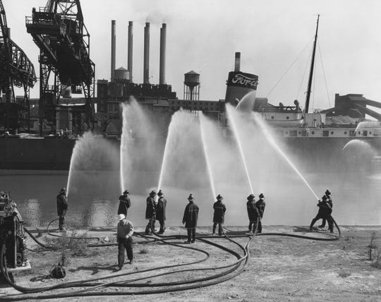 Firefighters train their hoses on a ship docked at the Ford Rouge Plant in 1958.  A huge, spreading fire at the plant in 1969 prompted concerns that that led to landmark environmental laws.