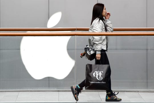 FILE - In this Feb. 26, 2019, file photo, a woman carries a paper bag containing goods purchased from American brand Abercrombie & Fitch walks past an Apple store at the capital city's popular shopping mall in Beijing. Companies who do business with China walk a fine line to stay aligned with U.S. values such as freedom of speech and democracy while avoiding offending China, where they stand to make billions of dollars.