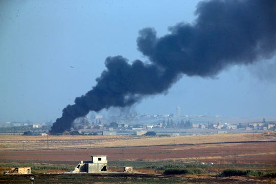 In this photo taken from the Turkish side of the border between Turkey and Syria, in Akcakale, Sanliurfa province, southeastern Turkey, smoke billows from a fire inside Syria during bombardment by Turkish forces Wednesday, Oct. 9, 2019. Turkey launched a military operation Wednesday against Kurdish fighters in northeastern Syria after U.S. forces pulled back from the area, with a series of airstrikes hitting a town on Syria's northern border.