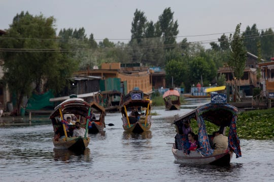 FILE - In this Saturday, Aug. 3, 2019, file photo, Tourists in Shikaras, a traditional gondola, cross the Dal Lake as they prepare to leave Srinagar, Indian controlled Kashmir. Authorities in Indian-controlled Kashmir are allowing tourists back into the region two months after ordering them to leave, citing security concerns.
