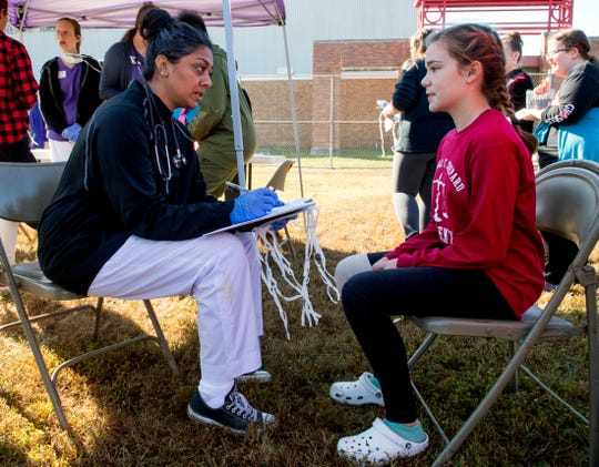 "Volunteer Jaimie Sheth, left, puts Harrison High School Freshman Bella Albright, right, through a mental evaluation during the ""Walk a Mile in My Shoes"" refugee camp simulation at Harrison High School Wednesday morning, Oct. 9, 2019."