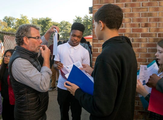"Global Human Project Founder Jud Hendrix, left, blows a whistle and ask student to show him their identification papers during the ""Walk a Mile in My Shoes"" refugee camp simulation at Harrison High School Wednesday morning, Oct. 9, 2019."
