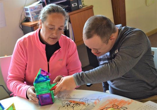 Engagment and inclusion are strong focuses at The MACC Center. Here, Direct Support Staff Leanne Sutkus helps Nick Werlins construct a house with magnetic tiles.