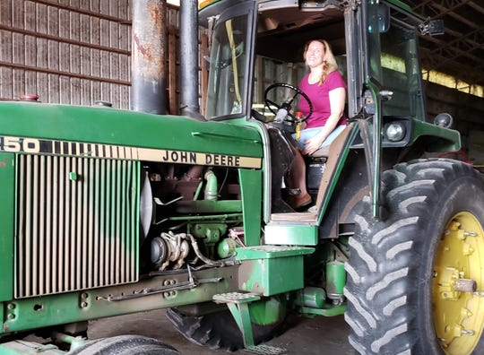 Sonya Zimmerman tries out the feel of driving a large tractor during the tour of Toussaint River Angus Farm.