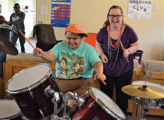 While volunteerism is a big focus at the MACC Center, the adults who come each day can find lots of recreational activities to do, too. Here, Timmy Juarez plays drums while Amanda Alley sings along.