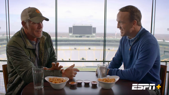 "Brett Favre, left, and Peyton Manning share football stories over cheese curds in a suite at Lambeau Field for an episode of ""Peyton's Places."""