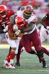 Florida State Seminoles defensive tackle Marvin Wilson (21) tackles Louisville Cardinals running back Trey Smith (12)  in this 2018 file photo.