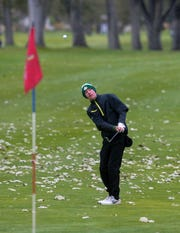 CMR's Eli Groshelle pitches on the green on the 17th hole during the Class AA State Golf Tournament at Meadow Lark Country Club on Tuesday.