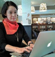 Japanese poet Arai Takako, shown working in the lobby of The Graduate Hotel, is one of 28 visiting writers spending the fall in Iowa City as part of the International Writing Program at the University of Iowa.