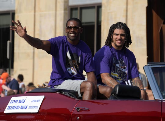 Aug 4, 2018; Canton, OH, USA; NFL former receiver Randy Moss (left) and presenter and son Thaddeus Moss acknowledge the crowd during the Pro Football Hall of Fame Grand Parade on Cleveland Avenue. Mandatory Credit: Kirby Lee-USA TODAY Sports