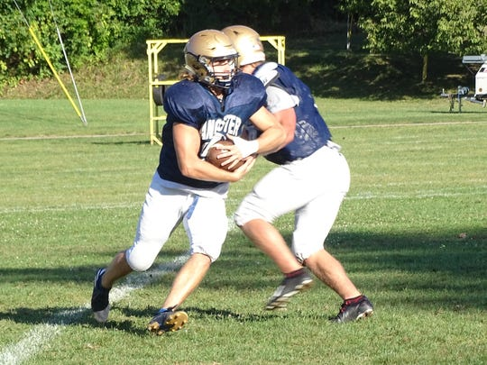 Lancaster senior running back Brock Thomas takes a hand off from quarterback Curtis Young during Lancaster's practice on Tuesday.