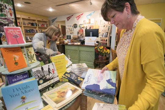 2 Dandelions Bookshop owners Jeanne Blazo, left, and Jeri Kay Thomas, shown Wednesday, Oct. 9, 2019, arrange books that follow the theme of the Brighton store's name.