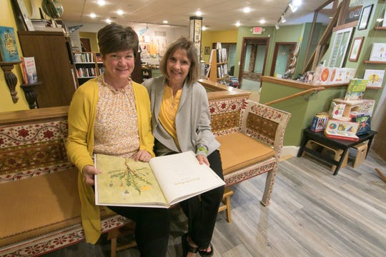 "Jeri Kay Thomas, left, and Jeanne Blazo sit on a bench on loan to the new 2 Dandelions Bookshop in Brighton Wednesday, Oct. 9, 2019. They hold a book entitled ""The Lost Words"" by Robert MacFarlane and Jackie Morris."