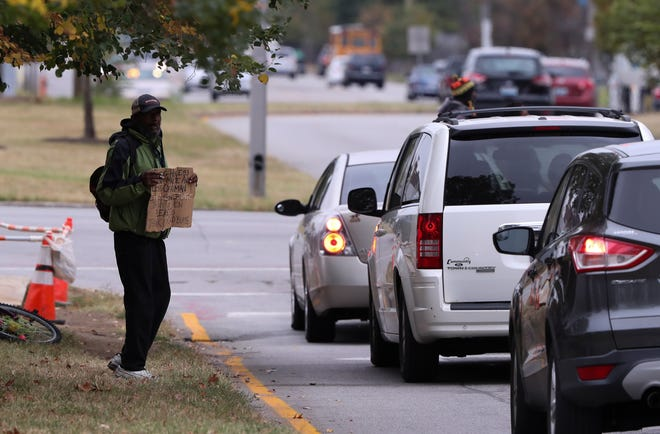 A man holds up a sign saying that he is homeless and would appreciate any help at the intersection of 9th and West Broadway on Oct. 9, 2019 in Louisville, Ky.