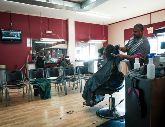"""""""I love this neighborhood,"""" Buel Williams, owner of BW's Hair Fashions said while working with a client Wednesday, Oct. 9, 2019, in his shop located in the shopping center near the southwest corner of West Holmes Road and Pleasant Grove Road.  He has been there for fifteen years."""