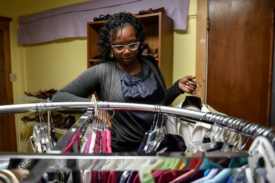 Charmane Bonaparte looks through business professional clothes at the Women's Center of Greater Lansing on Monday, Oct. 7, 2019, in Lansing.