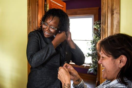 Charmane Bonaparte, left, tries on accessories picked out by employee Andrea Chavez, right, as Bonaparte tries on a dark suit at the Women's Center of Greater Lansing on Monday, Oct. 7, 2019, in Lansing.
