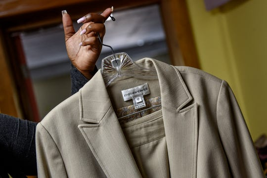 Charmane Bonaparte holds onto a beige suit she found while shopping for business professional clothes at the Women's Center of Greater Lansing on Monday, Oct. 7, 2019, in Lansing.