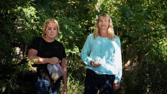 "Michele Pursley, left, of Meridian Township, and Laura Luptowski Seeley, of Haslett, pictured Monday, Oct. 9, 2019, near a wooded area just west of Big Lots in Okemos, where three stray, or what they refer to as ""community cats"" live."