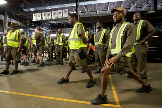 Delivery driver William Jenkins (right) stretches before their morning communications meeting Wednesday, Oct. 9, 2019, at UPS' package center and hub on Carrier Street in Memphis.