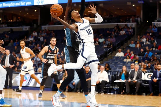 Memphis Grizzlies guard Ja Morant tries to lay the ball up past New Zealand Breakers center Ater Majok during their game at the FedExForum on Tuesday, Oct. 8, 2019.
