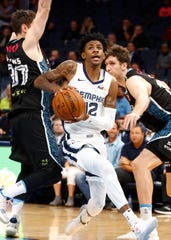 Memphis Grizzlies guard Ja Morant splits New Zealand Breakers defenders Jarrad Weeks, left, Robert Loe during their game at the FedExForum on Tuesday, Oct. 8, 2019.