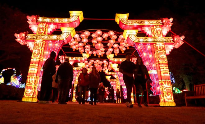 People walk through a tunnel of lights near the entrance at the China Lights lantern festival at Boerner Botanical Gardens in Hales Corners on Oct. 8, 2019. The festival was canceled for a second consecutive year.