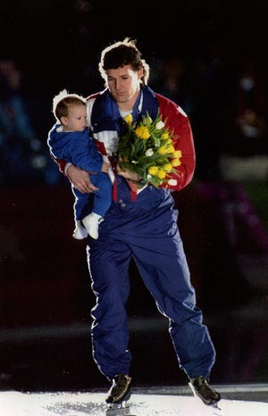 Dan Jansen skates with daughter Jane in his arms after winning the speedskating 1,000 meters at the 1994 Olympics.