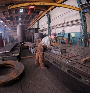 A worker labors at Monarch LLC, a heavy manufacturer on Milwaukee's northwest side that has gone into receivership.