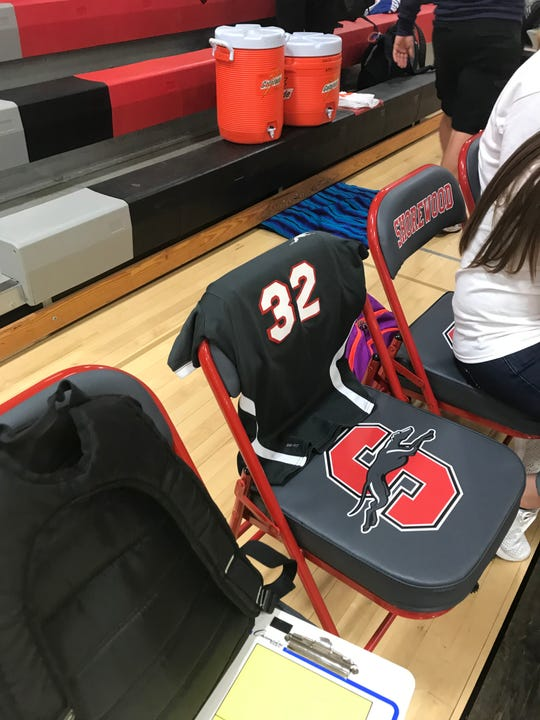 A chair on the Shorewood High School girls' volleyball team's bench was left open to honor Megan Frieseke Oct. 8. Her No. 32 jersey is draped over the chair.