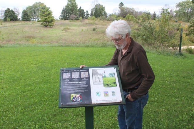Bill Mueller pauses next to a sign at the Western Great Lakes Bird and Bat Observatory in Port Washington, Wis. Mueller is retiring as director of the organization, which helped oversee restoration of wildlife habitat at the site of a former golf course.