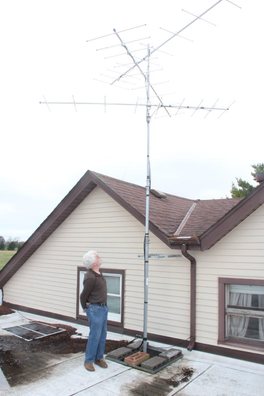 Bill Mueller of Milwaukee inspects a Motus receiver on the roof of the Western Great Lakes Bird and Bat Observatory in Port Washington, Wis. The Motus project tracks movements of birds fitted with small radio transmitters called nanotags.