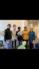 Dr. Tomasz Czeschura, Filip Forsberg, Vessie Moore, Mikael Granlund and Dr. Melissa Meier pose during a surprise Predators visit at Interfaith Dental Clinic on Monday, Oct. 7, 2019,