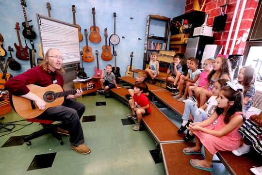 Thurman Francis Arts Academy music teacher Michael Thiemann sings with a group of first graders on Oct. 2.