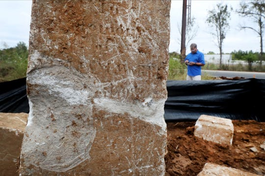 Writing and damage can be seen to an obelisk from a pre-Civil War cemetery, on Tuesday Oct. 8, 2019. The tombstones above the graves were bulldozed recently when a construction company cleared land that included the cemetery hidden by rocks and  weeds for the future site of The Outpost Armory and Murfreesboro Indoor Indoor Range. Work has been stopped on the site while the tombstones are recovered from a pile of debris.