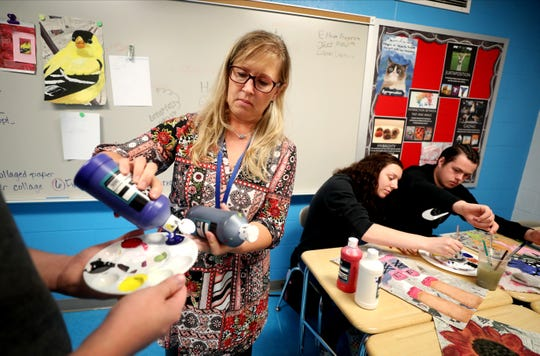 Stewarts Creek art teacher Rebecca Fraser, who had to move from room to room to teach last year, now has her own classroom. Fraser passed out paint and helps students with their projects on Oct. 2 in her new classroom.