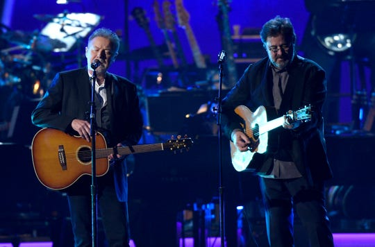 "FILE - This Feb. 8, 2019 file photo shows Don Henley, left, and Vince Gill performing ""Eagle When She Flies"" at MusiCares Person of the Year honoring Dolly Parton in Los Angeles. Eagles, with Deacon Frey and Vince Gill,  are planning massive performances of their album ""Hotel California"" during their 2020 tour. Performances of the band's 1976 album will include a 46-piece orchestra and a 22-voice choir. Organizers announced Tuesday that in total, 77 musicians are expected to be onstage while Eagles perform hits from the album including ""New Kid in Town"" and ""Life in the Fast Lane."" (Photo by Chris Pizzello/Invision/AP, File)"