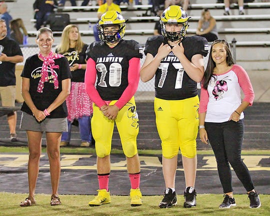 October is cancer awareness month and as a special tribute, Fairview High School football Captains #20 Jacob Clevenger and # 77 Conner Ferris escort two cancer survivors, Bonnie Helgesen and Brandi Maige, onto the football field for the coin toss before the 'Pink Out' game Oct. 4, 2019.