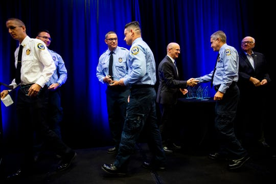 Members of Collier County Emergency Medical Services shake hands with Michael Dalby, president of The Greater Naples Chamber of Commerce, after receiving the emergency medical services award during the Distinguished Public Service Awards hosted by The Greater Naples Chamber of Commerce at the Hilton Naples on Wednesday, October 9, 2019.