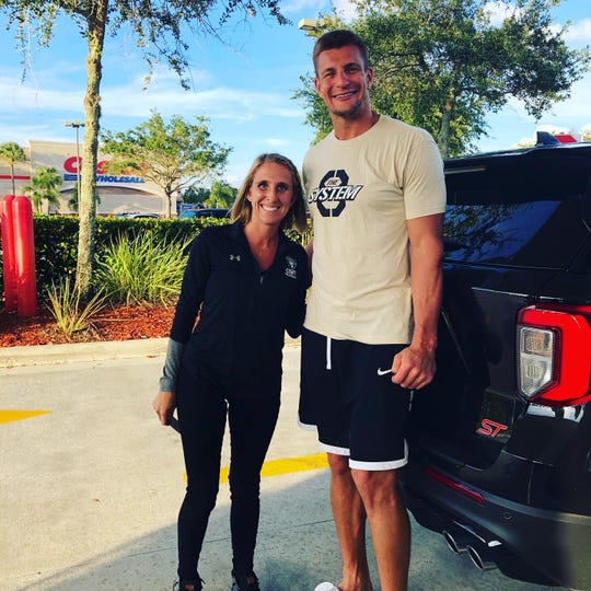 Community School volleyball coach Alicia MacIntyre poses with retired New England Patriots star Rob Gronkowski after meeting pumping gas at the Gulf Coast Town Center Costco.