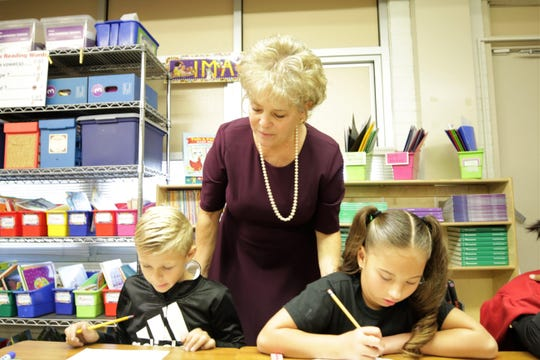 Apache Elementary School Third Grade Teacher Nancy Brummell checks on Tyrus Williams, left, and Sophie Christensen, right, classwork on Oct. 9. Brummell is a finalist for the New Mexico Teacher of the Year award.